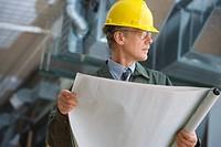 Businessman in hard hat holding blueprints