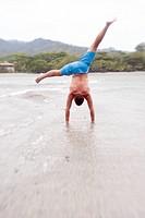 Man Doing Cartwheel on Beach