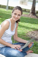 Happy girl using laptop outside