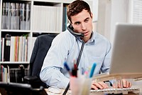 Young man on telephone and working on laptop