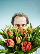 A man nervously hiding behind a bouquet of tulips