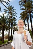 Spain, Mallorca, Palma, Young woman eating ice cream, smiling