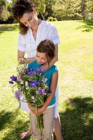 Mother standing with daughter holding flowers