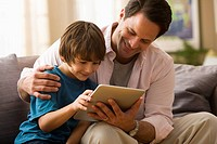 Caucasian father and son using digital tablet together