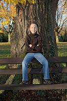 Germany, Bavaria, Girl sitting on bench with arms crossed, portrait