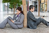 Germany, Leipzig, Business people sitting at tree with digital tablet and cell phone