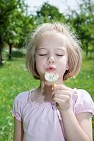 Girl blowing on a dandelion clock
