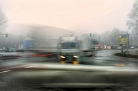 Trucks and cars at an intersection in the morning mist, motion blur