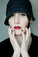 Close_up portrait of a young woman with pale skin and brown eyes, with a vintage hat and red lipstick staring at the camera