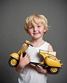 Five-year-old boy holding a toy Vespa scooter, gift, happy face