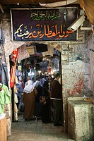 Shoppers and signs at a market in the old city section of Jerusalem