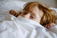 Boy lying in bed with bed sheet covering face
