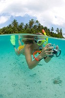 Image, half above, half under water, young woman snorkeling and taking pictures in the lagoon of Biyadhoo Island, South Male Atoll, Maldives, Indian O...