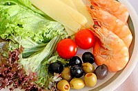Salad plate of cheese, olives, tomatoes, shrimp and lettuce on white plate with green trim  White tablecloth  Green and black olives  Full frame