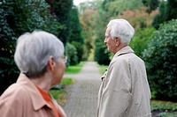Senior caucasian woman with glasses looking at senior man, seen from backside, blurred green background, Hamburg, Germany, Europe