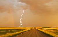 electrical storm over gravel road between farmland, near Val Marie, Saskatchewan