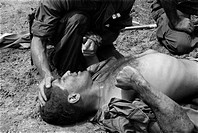 Vietnam War. US Marine wounded by a Viet Cong booby trap is comforted by a fellow Marine. 1967.