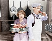 Couple standing together in a kitchen with a cooked turkey All persons depicted are not longer living and no estate exists. Supplier warranties that t...