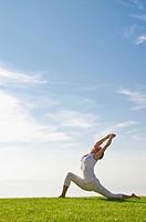 Young woman practising Hatha yoga outdoors, showing the pose anjaneyasana, chandrasana, half moon pose, Nove Mesto, Okres Teplice, Czech Republic, Eur...