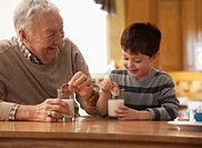 Caucasian grandfather and grandson eating milk and cookies