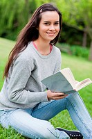 Young smiling girl holding a book while sitting on the grass and looking at the camera