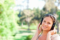 Smiling young woman in the park listening to music