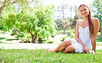 Smiling young woman sitting on the lawn in a park