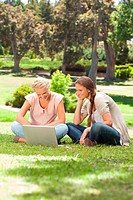 Smiling female friends with a laptop sitting on the lawn