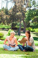 Female friends reading their books in the park