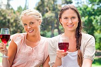 Smiling female friends having red wine in the park