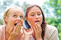 Curious female friends listening to phone call in the park