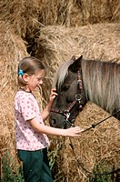 Girl with Shetland Pony / Shetty, straw, bridle