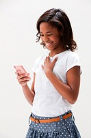 African American girl laughing and holding cellphone, studio shot