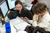 Two women checking paperwork in their cubicle