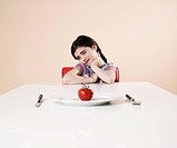 Girl looking with disgust at the tomato on her plate