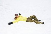 Girl in yellow jacket lying in snow