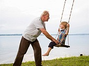 grandfather with grandson on swing