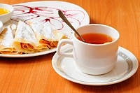 Tea and pancakes with powdered sugar