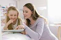 Mom and daughter surfing the net together.