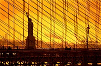 USA, New York, statue of the Liberty behind the Brooklyn bridge.