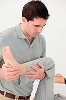 Chiropractor holding the leg of his patient while moving it in a room