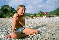 Shy young girl on beach covering her breasts
