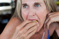 57 year old woman biting into a lemon