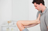 Chiropractor raising the leg of his patient against his chest in a room