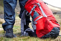 hiker hillwalker wearing boots waterproofs and rucksack in the highlands of Scotland UK