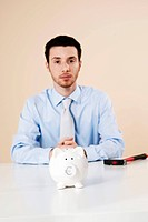 Young man with a concerned expression sitting behind a piggy bank