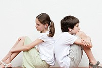 Boy and girl sitting back to back listening to music together