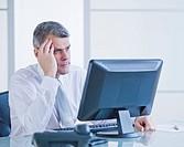 Portrait of worried businessman working at desk
