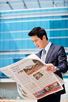 Asian Businessman Reading Newspaper