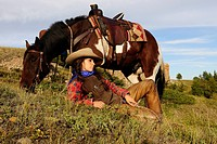 Cowgirl lying in the grass, her horse standing next to her, Saskatchewan, Canada